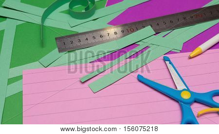 ruler and scissors and hand cut paper straps on colorful scrapbook