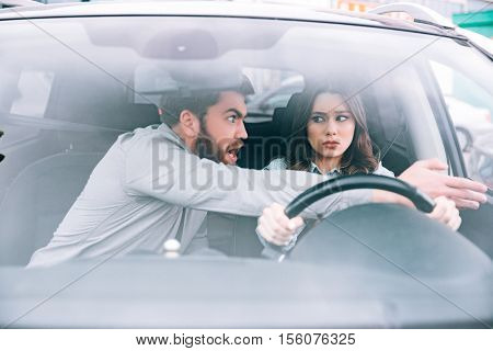 Irritated woman and man in car. front view. woman at the wheel