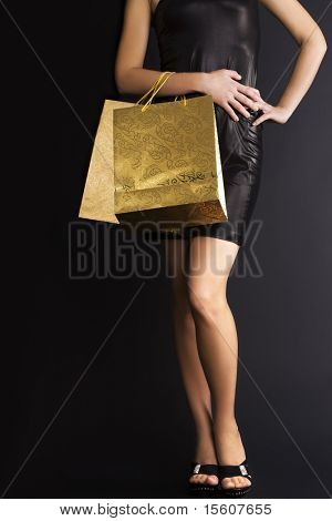 Elegant woman with golden holiday shopping bags. Space for text.