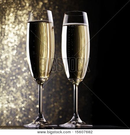Champagne flutes on holiday background. Space for text.