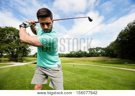 Focused man playing golf in golf course
