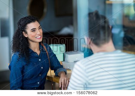 Smiling young couple sitting at counter and interacting in café