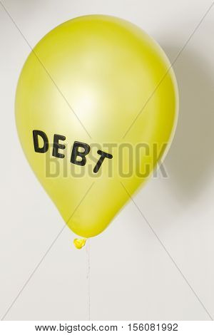 Yellow balloon with the word debt representing the economic, financial and consumer debt bubble.