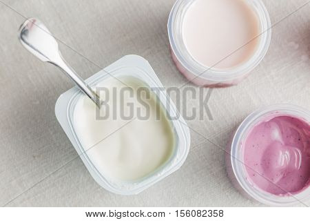 Natural And Fruit Yoghurts Assortment  In Plastic Bowls On White Textile Background. Healthy, Diet,