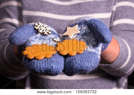Woman offer two cookies. There is mitten on her hands