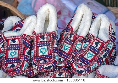 Multicolored house slippers made of woven wool and exposed in bulk for sale.