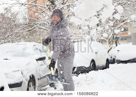 Man shoveling her parking lot after a winter snowstorm.