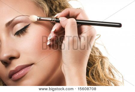 Makeup artist applying flesh-coloured eyeshadow