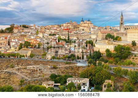 Old city of Toledo with Primate Cathedral of Saint Mary, churches of San Ildelfonso, San Roman and Santo Tome at sunset, Castilla La Mancha, Spain. Restoration of the Arab baths in the foreground