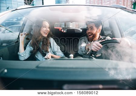 Enjoy couple in car. man at the wheel. front view. eyes to eyes