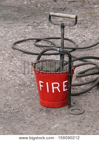 A Vintage Fire Bucket with a Hand Operated Pump.