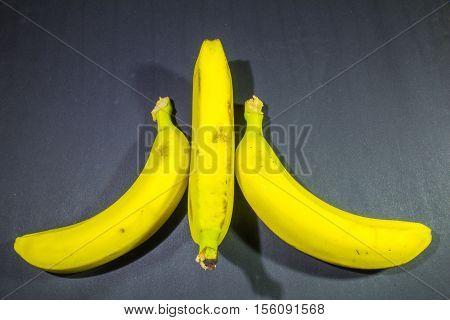 Three Mature Bananas On Dark Gray Background
