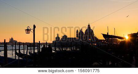 Romantic Italian city of Venice in sunset. World Heritage Site. Traditional Venetian wooden boats, gondolier and Roman Catholic church Basilica di Santa Maria della Salute.