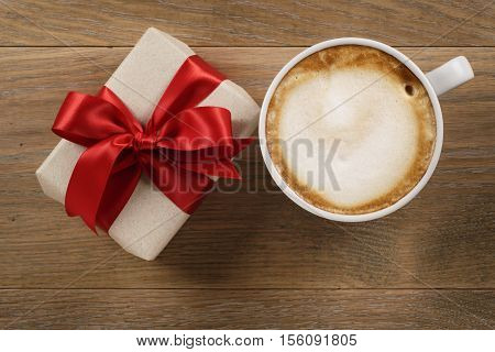 cup of cappuccino and gift on wooden oak table top view, shot directly above