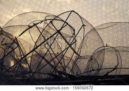 Silhouette of old fishing nets against sunrise sky
