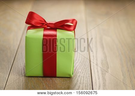 green paper gift box with classic red ribbon bow on wooden table and copy space for your info