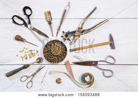 Leather craft tools on a white wooden background