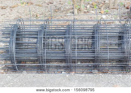 Rolls of steel wire mesh on the ground horizontal photo.