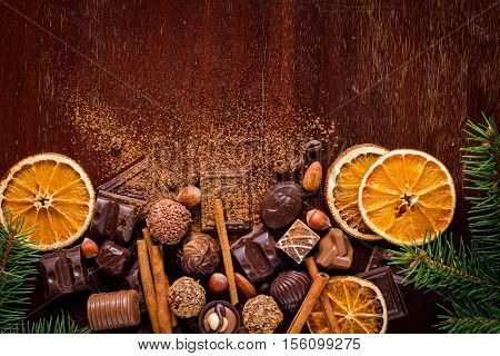Christmas sweets, chocolates, spices, chocolate truffles and dried oranges on wooden backgroun with copy space for text. Horizontal