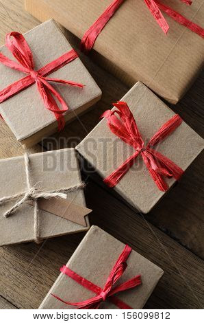 Overhead shot of multiple simple lidded boxes tied with red raffia ribbon bows and string. One has a blank tag for your message. Oak plank table below.