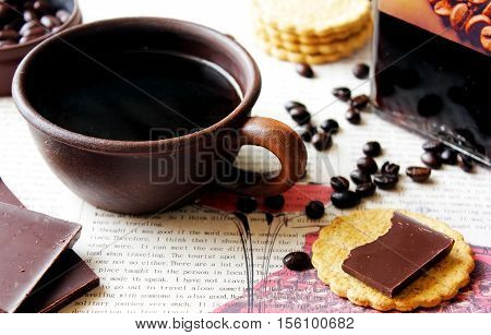 Black espresso coffee with biscuits and a morning newspaper