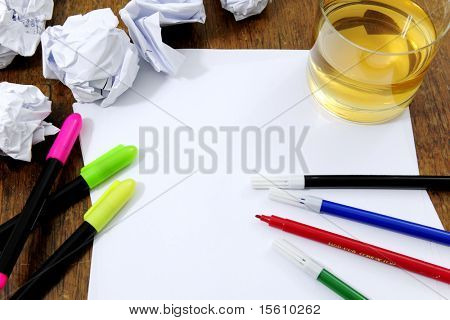 creativity problems: blank paper on desk with many paperballs  and whiskey