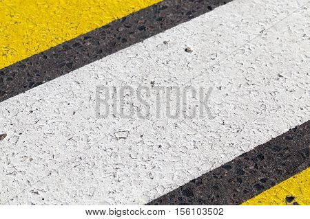 photographed close-up of road marking is located on the roadway, frayed yellow and white stripes of a pedestrian crossing