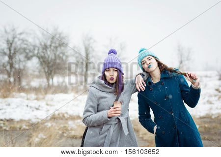 Two cheerful teenage girls outdoors in winter having fun. Female friends enjoying winter in park, drinking coffee, wearing colorful lipsticks, hats and coats. Natural lighting, mild retouch.