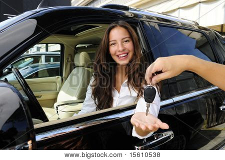 businesswoman receiving keys of her new status car from dealer