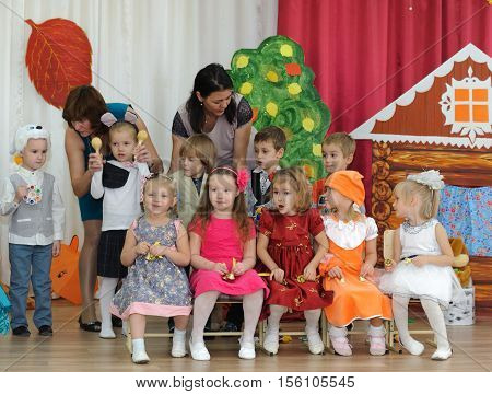BALASHIKHA RUSSIA - OCTOBER 26: Ten small children dressed in carnival costumes and two adult women taking part in autumnal matinee in kindergarten on Zarechnaya Street on October 26 2016 in Balashikha.
