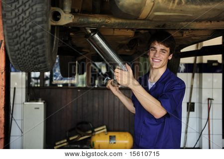 happy car mechanic working at the car  repair  shop