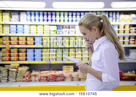 woman reading her shopping list in the supermarket with copy space