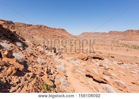 Twyfelfontein, Namibia - August 27, 2016: Group Of Tourists Walking In The Desert At Twyfelfontein,
