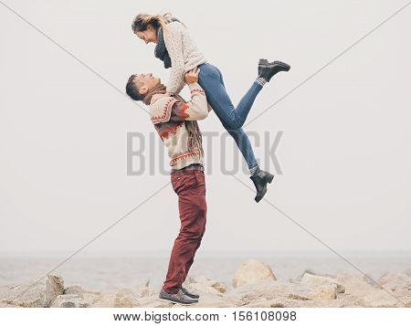 Young attractive couple in knitted sweaters on a cliff on sea shore man hold his girfriend on his hands in the air creative toning