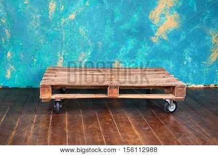 Empty wooden pallet in loft interior with grunge walls