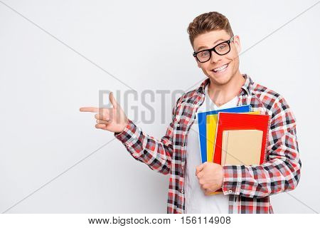 Young Smart Happy Student With Books Pointing On Copy Space