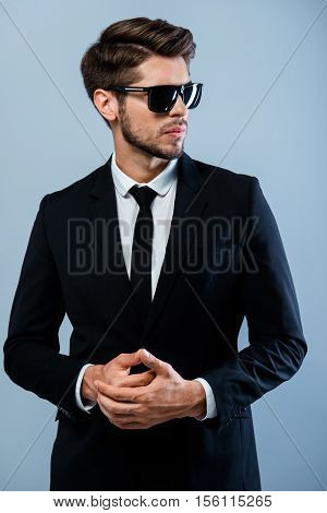 Brutal Man In Black Suit And Glasses With Clasped Hands