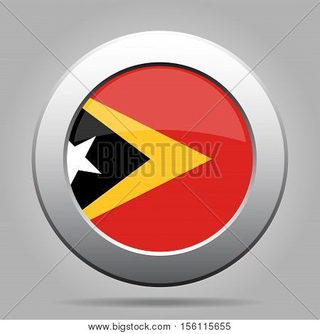 National flag of East Timor. Shiny metal gray round button with shadow.