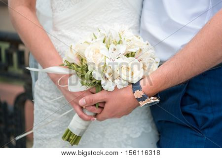 Hands newlyweds with a bouquet. A newly weding couple place their hands on a wedding bouquet