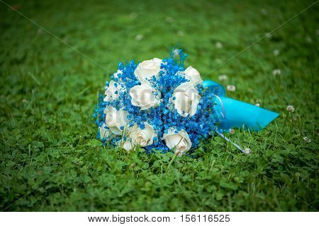 Bridal bouquet. The bride's bouquet. Beautiful bouquet of white, blue, pink flowers and greenery, decorated with long silk ribbon, lies on vintage wooden chair