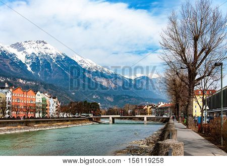 Innsbruck, Tirol, Austria. Inn river bridge historic houses Alps covered with snow and tress in winter