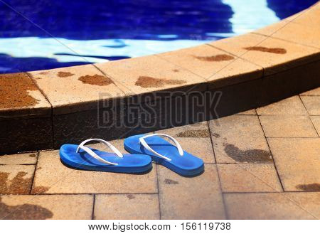 A pair of blue flip flops by a pool