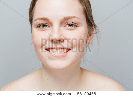 Young Beautiful Freckles Woman Face Portrait. Gray Background.