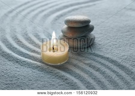 light warm candle and cool stone on sand