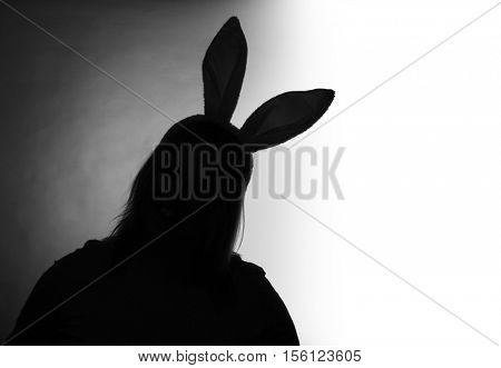 Silhouette of young girl with rabbit ears. Children abuse, domestic violence and neglected child concept. Black and white photography. Picture with space for your text.