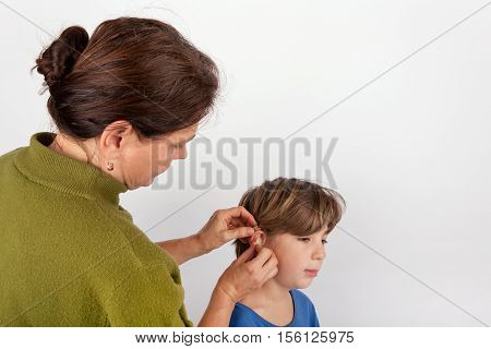 Woman audiologist fitting a young boy with hearing aid