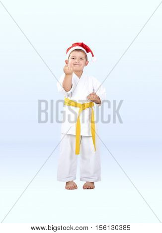 Little karateka in a cap of Santa Claus is in the rack karate