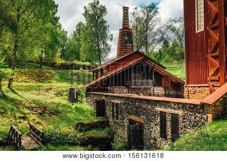 Old red ironworks building. standing in the lush green environment. poster