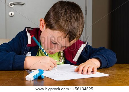 Young child learns to write and practices by writing letters and short words on a paper with a pencil