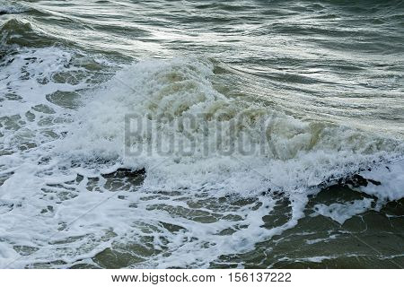 Waves breaking on shore during winter with low sun shining on water.